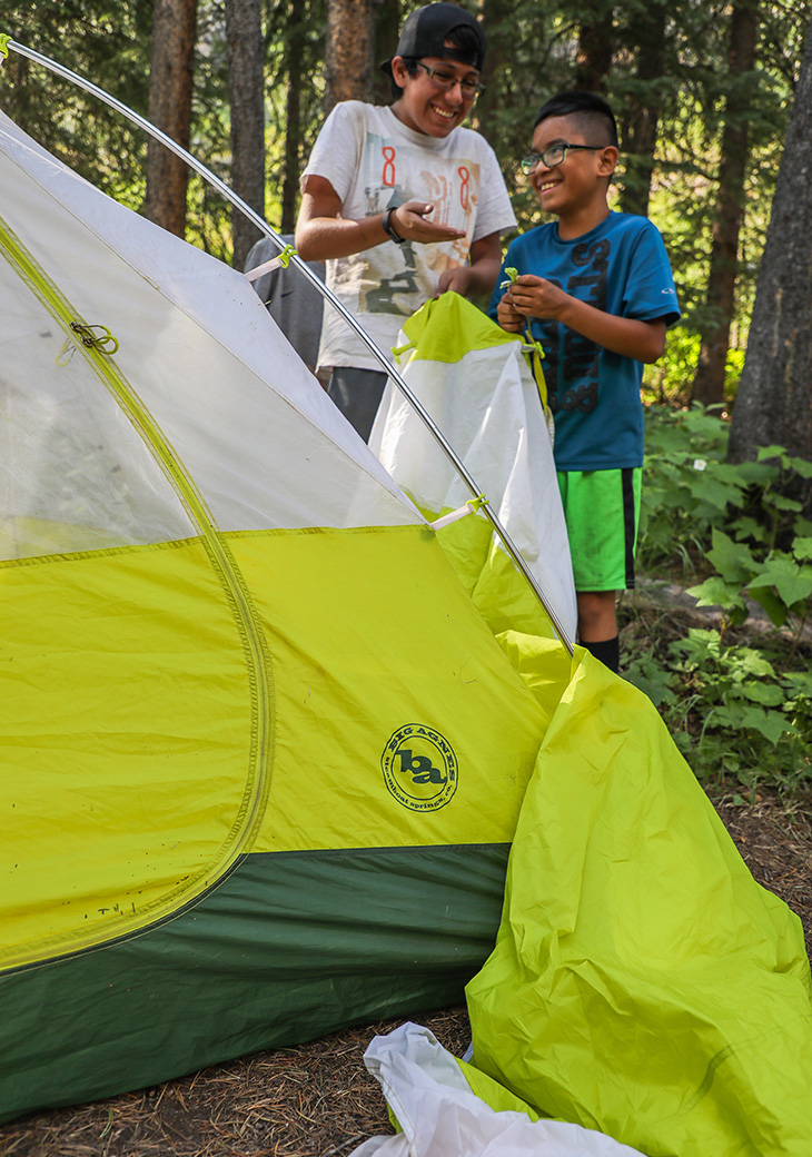 Two young backpackers setting up their backcountry-home for the night while also following Big Agnes' number one rule of backpacking - have fun!